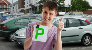 Young male student holding green driving pass plate