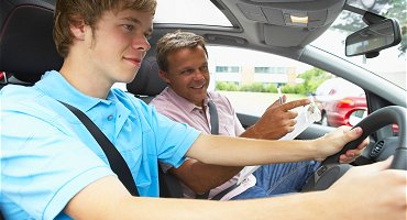 Young male driver with driving instructor